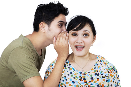 Young asian man whispering a secret news to his girlfriend. isolated on white photo