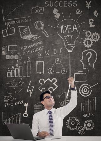 inteligencia: Hombre de negocios que tiene una idea con la computadora port�til en el escritorio