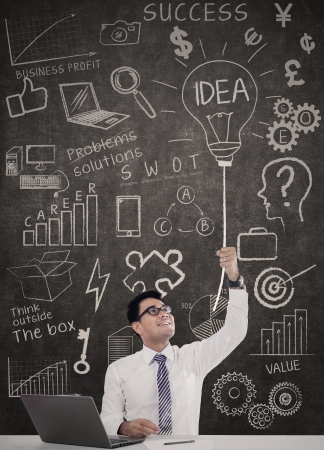 lightbulb: Homme d'affaires ont eu une id�e avec un ordinateur portable sur le bureau