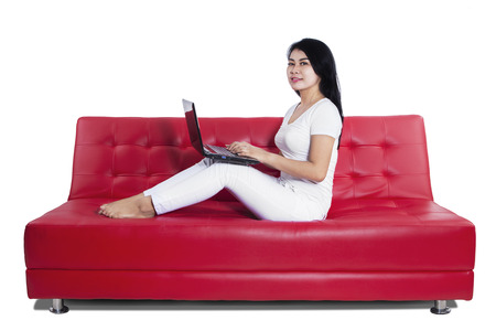 Young asian woman on a sofa working with a laptop - isolated on white background Stock Photo - 24906957
