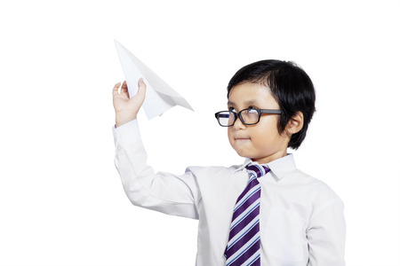 Photo of little businessman holding paper aircraft in stretched hand before launching it photo