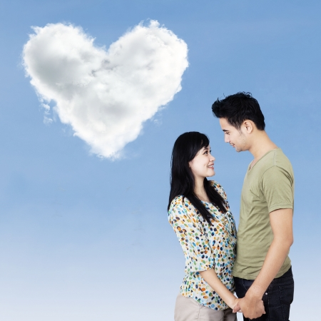 Romantic couple smiling under clouds shaped of heart in blue sky photo