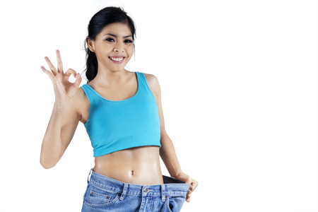 Happy woman showing her weight loss by wearing an old jeans Stock Photo