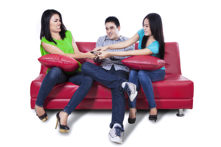 Three young people fighting for remote control - isolated on white background Stock Photo - 24907247