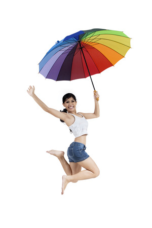 Happy woman jumping with rainbow umbrella isolated on white background photo