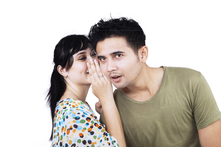 Youang asian woman whispering a secret news to her boyfriend photo