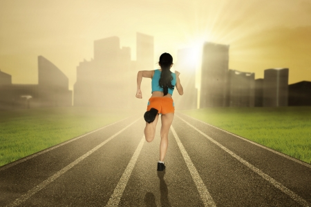 Athlete woman running on the track with cityscape background photo