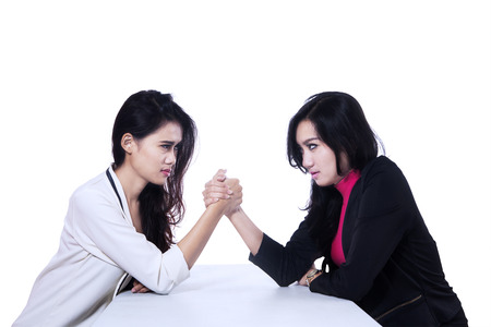 Businesswomen in arm wrestling gesture on working table. isolated on white photo