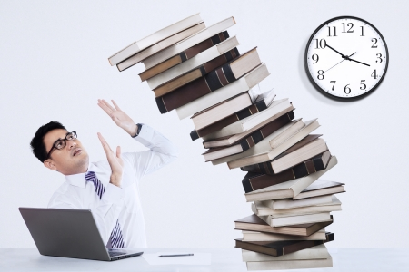 workaholic: Businessman overworked with pile of books in the office Stock Photo