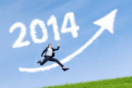 Business woman jumping over arrow sign with 2014 on the grass photo