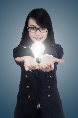 Business woman with a lit light bulb in her hand (idea concept) photo