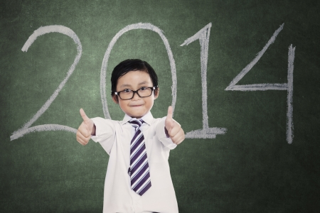 Portrait of little boy giving thumbs up in classroom photo