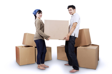 Young couple moving into new home carrying box. isolated on white photo