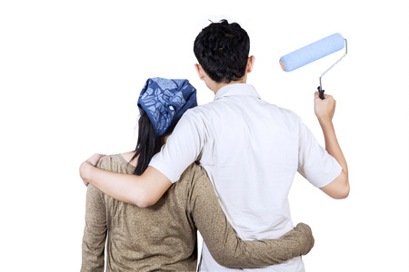 Rear view of young couple looking wall and ready to painting the wall. isolated on white photo