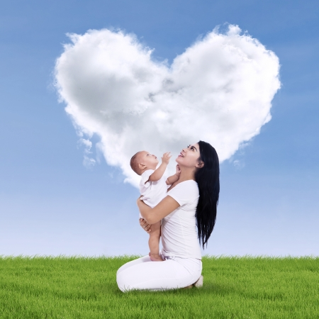 Portrait of sweet baby and his mother with heart shaped cloud Stock Photo - 24907626