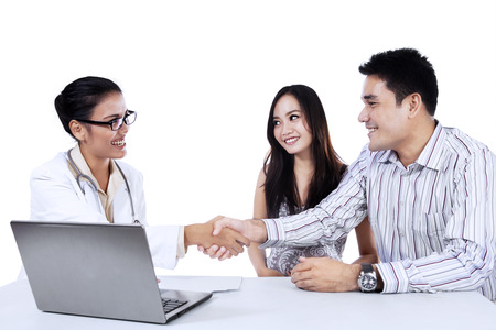 Female doctor shaking hands with a couple isolated on white background photo