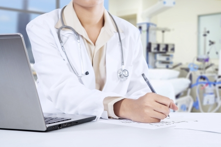Female doctor writes notes in the hospital