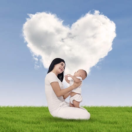 Portrait of sweet baby and his mother with heart shaped cloud photo