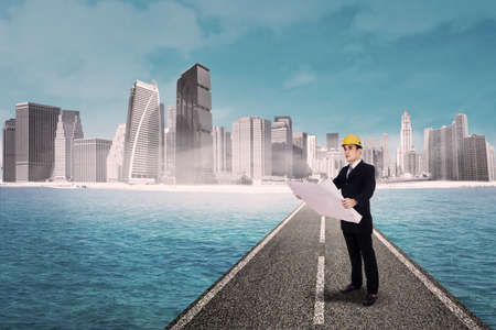 Man holding blueprint and standing on the road with cityscape background photo