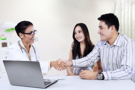 Medical doctor shaking hands with a couple in doctors room photo