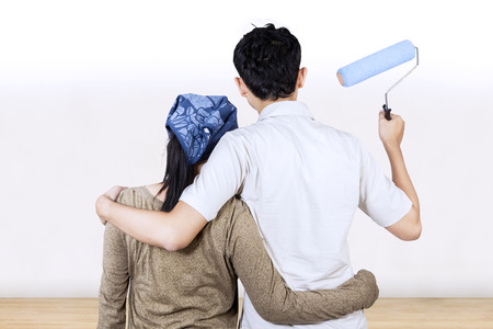 Rear view of young couple looking wall and ready to painting photo