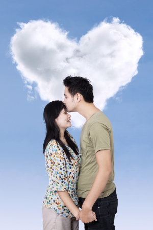 Young man kissing his girlfriend over heart shape cloud photo