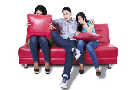 they are watching: Three young people watching TV a horror movie and they are scared