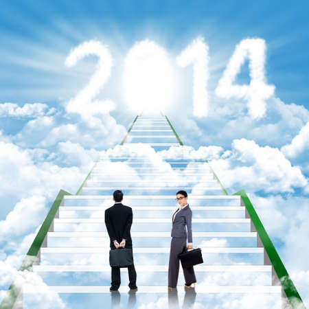 Two business people walking on the ladder leading upward to the new year 2014 photo