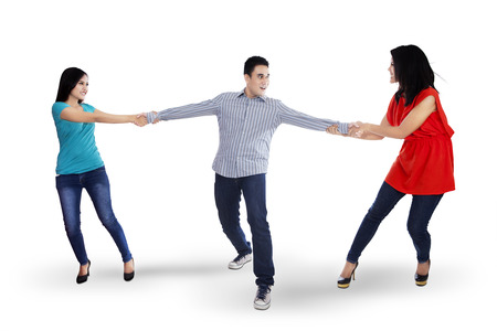 relationship problem: Two angry woman fighting for a man, isolated over white background Stock Photo