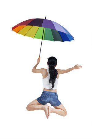 Woman jumping with rainbow umbrella isolated on white background photo