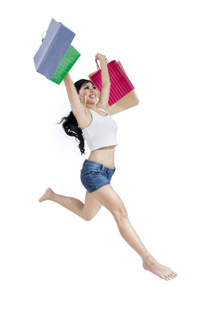 Beautiful woman with shopping bags in her hand, jumping on white background photo