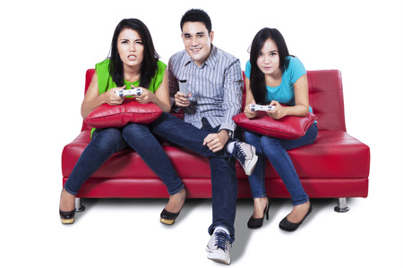 Group of young friends playing video games sitting on red sofa photo