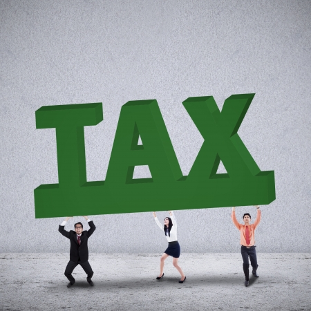 employe: Business team lifting a big word of TAX on grey background