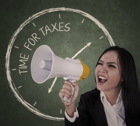 announcing: Businesswoman announcing time for taxes using megaphone