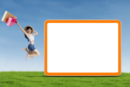 Portrait of attractive shopaholic jumping near copy space photo
