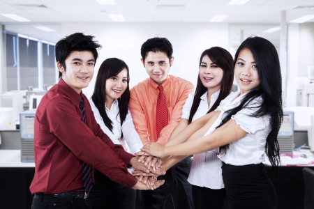 Asian business team showing unity by joining their hands together photo