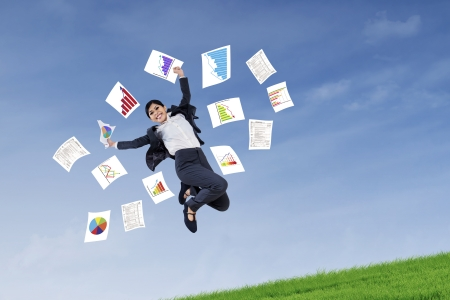 throw paper: Excited business woman jumping and throwing papers on the meadow Stock Photo