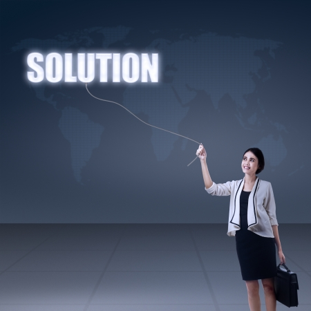 Beautiful businesswoman holding a solution on world map background photo