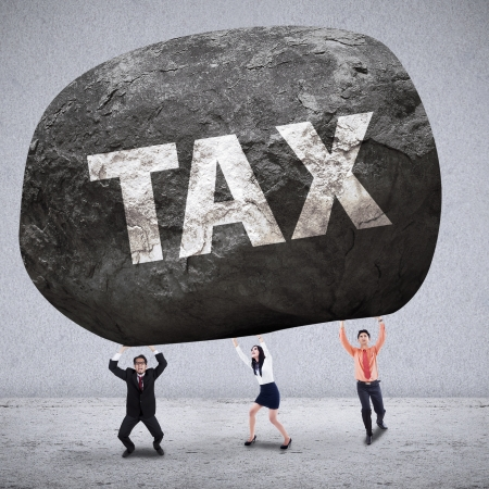 Business team lifting the stone of TAX on grey background photo