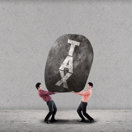 Businessmen lifting the stone of TAX on grey background photo