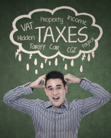 Concept of taxes with a stressed businessman for paying his taxes Stock Photo
