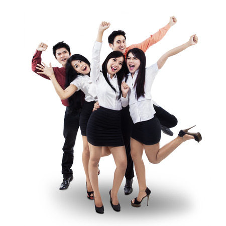 young entrepreneurs: Successful business team celebrating with arms up - isolated over white Stock Photo