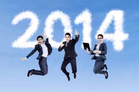 Portrait of excited businesspeople jumping on the sky over numbers of new year 2014 photo