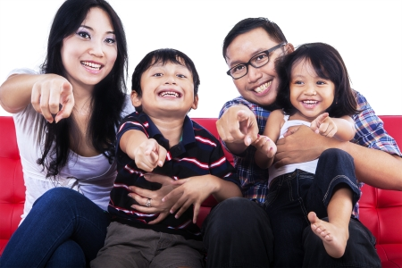 filipino adult: Family pointing at you and sitting on red sofa