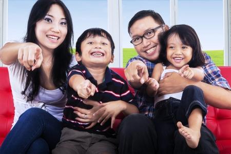 あなたに幸せな家族を指して、赤いソファーに座っていた