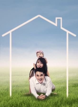 Happy family lying on grass field surrounded by home drawing