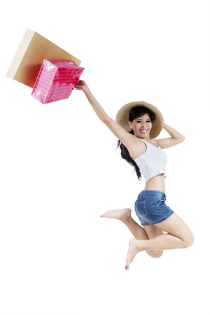 Happy shopping young woman jumping with color bags, isolated on white Stock Photo - 25067114