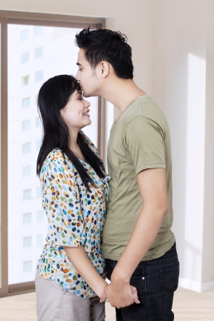 new love: Young husband kissing his wife in a new home Stock Photo