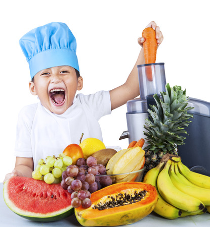 Little boy making healthy fruit juice with electric juicer on white background photo