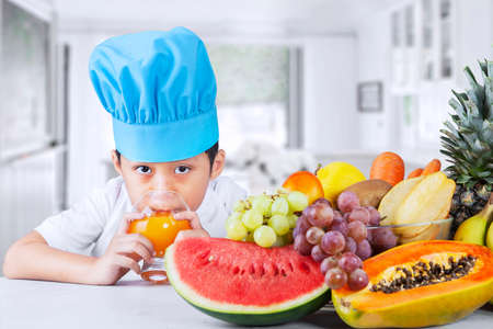 multivitamin: Little boy with fresh fruits and drinking juice at kitchen Stock Photo